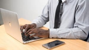 man behind a laptop with phone
