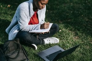 black college student behind laptop studying